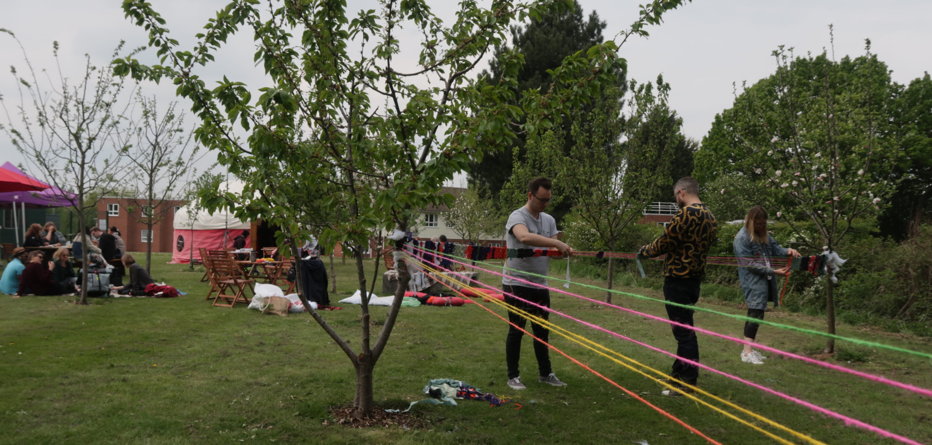 People engaged in activities: they are attaching coloured pieces of string to young trees in a green area