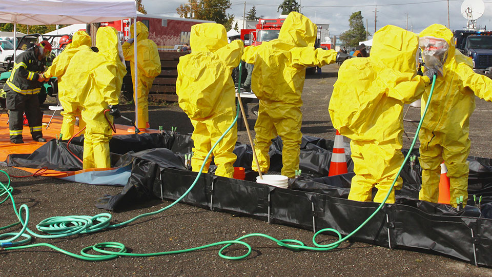 People in chemical protection suits being cleaned after an exercise