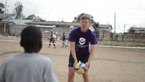 student playing sport with child in zambia