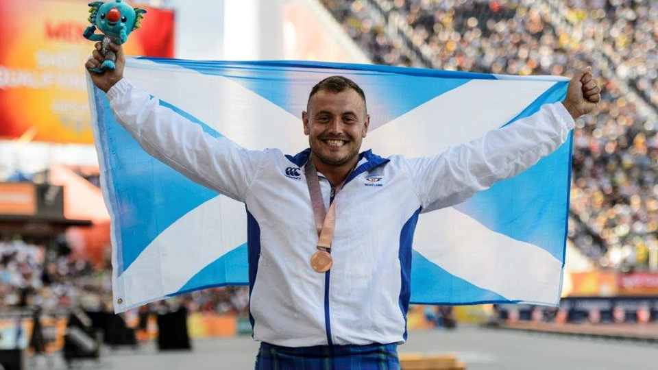 a man holding the Scottish flag