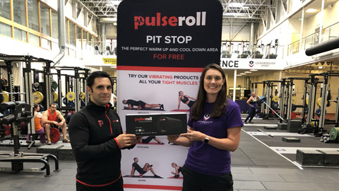 two people standing in the gym in front of a Pulseroll banner