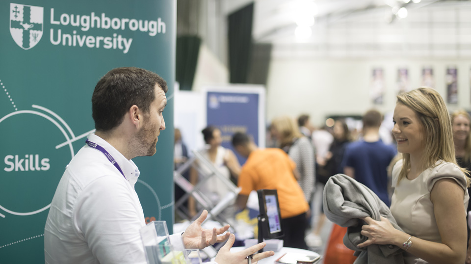 a woman talking to the man on the Loughborough University stand