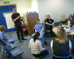 An engineer discusses the new mirror with stakeholders, midwives and (seated) a new mum