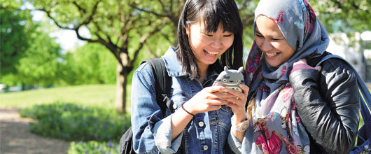 Two international students looking at a mobile phone