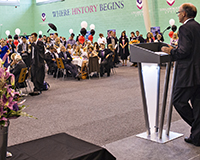 Photo of the 2014 summer graduation with Dean Angus Laing at the podium