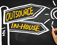 writing on a blackboard saying 'Outsourcing vs In-house'