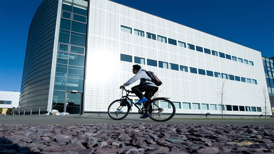 A male student on a bike in front of a building on campus