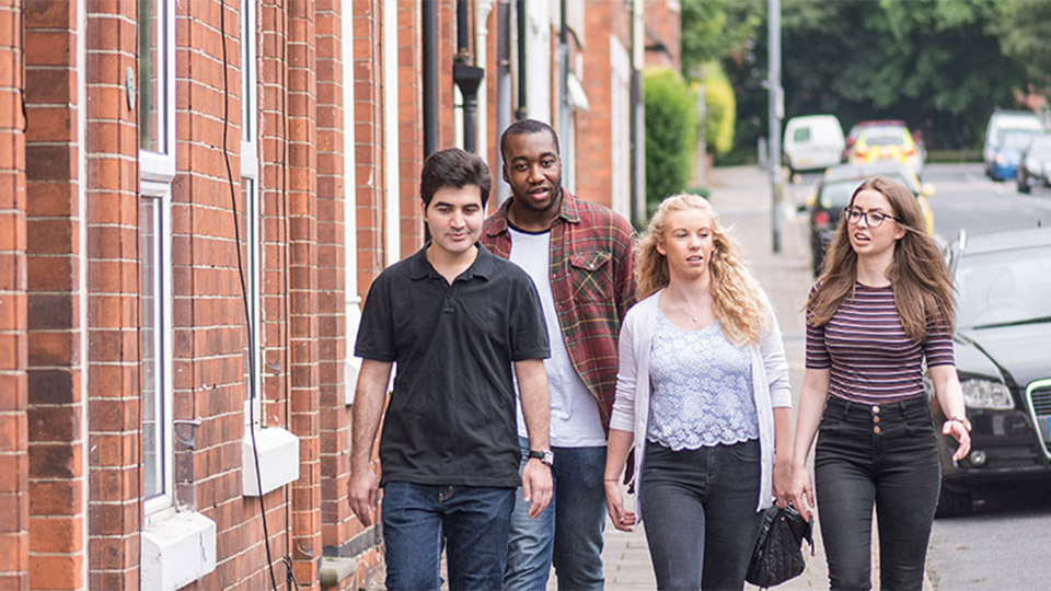 Four students walking along a residential street