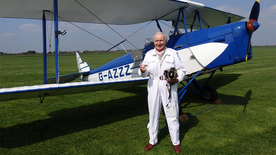 Pictured is Captain Desmond Penrose with a DH82a Tiger Moth.