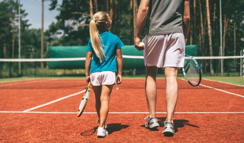 A father and daughter prepare to play a game of tennis