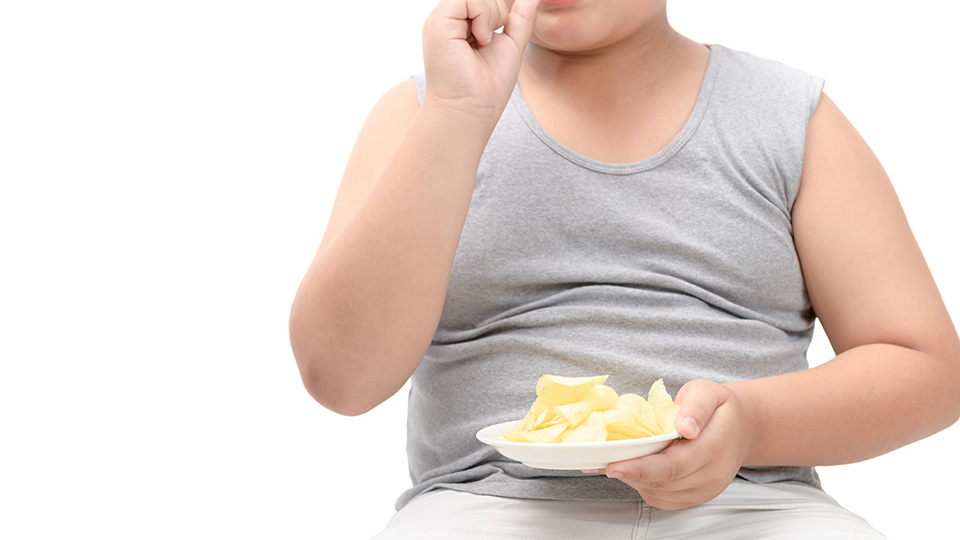 Pictured is a child eating crisps.