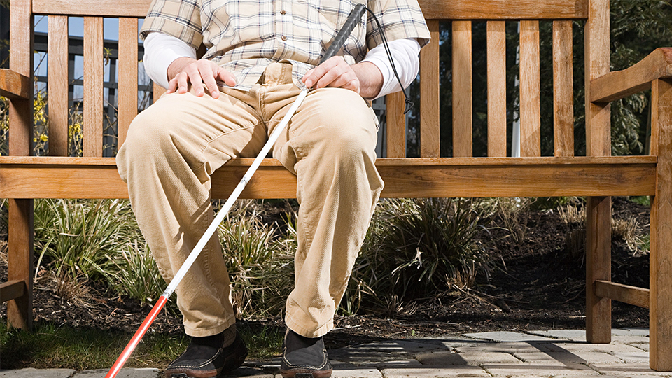 photo of a visually impaired person sat on a bench