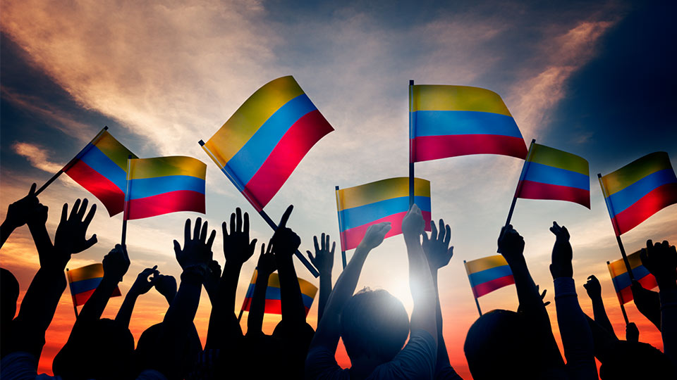 Pictured is a group of people waving the Colombian flag.
