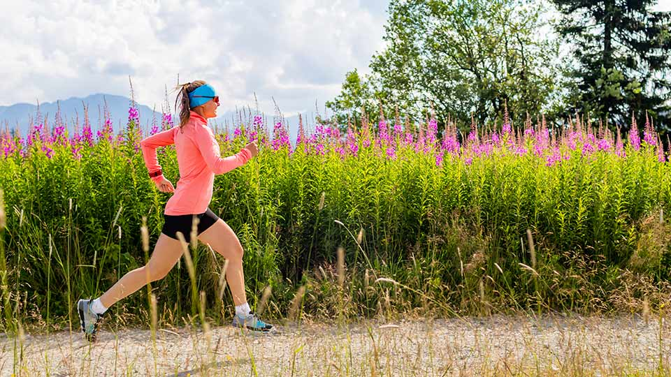 Pictured is a woman running next to a field of flowers.