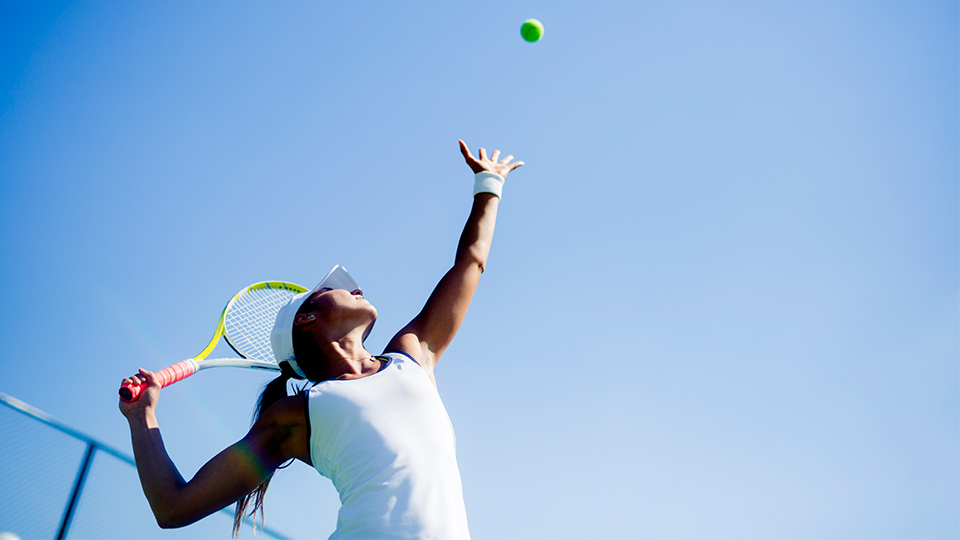 A woman hitting a tennis ball.
