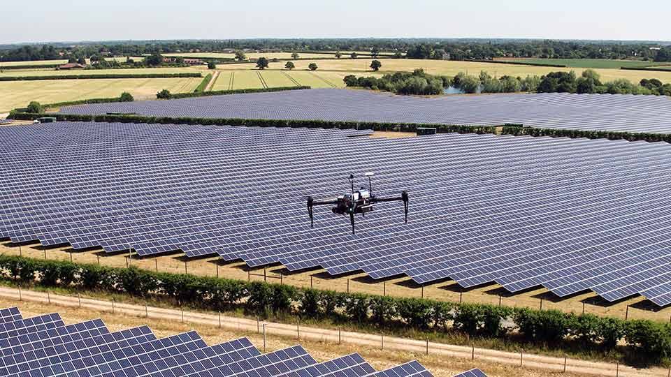 A drone flying over a solar panel farm. Image courtesy of Above.
