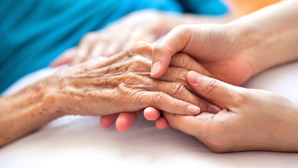 A young person holding an old person's hand