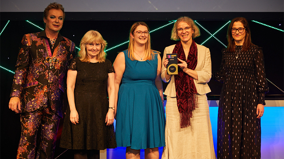 Photo of Academic Registry team members collecting their award at the Times Higher Education awards