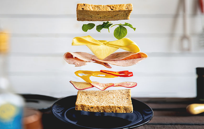 A sandwich with its ingredients above it in the air