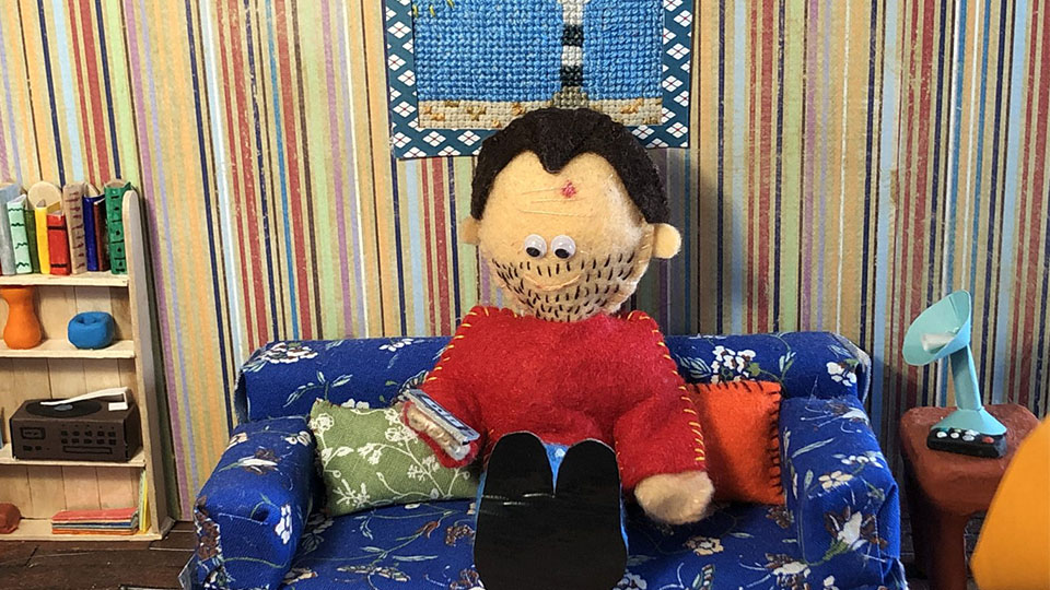 image of handmade puppet sat on a handmade sofa in a room created by student Amy Begent