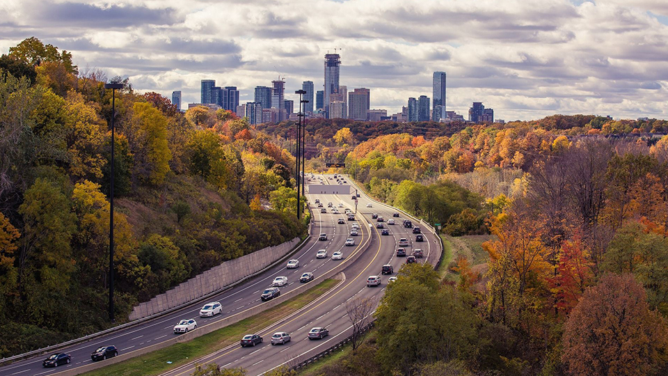 photo of a busy highway with backdrop of city and buildings