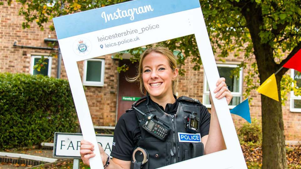PC Charlotte Dickens with Instagram sign outside university hall of residence