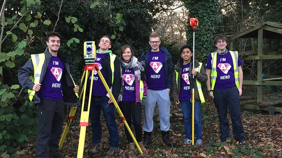Engineering students helping outdoors with scouts building project