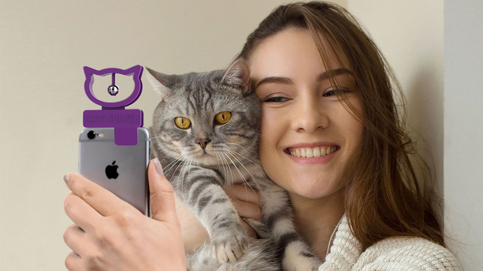 photo of cat selfie accessory clipped to a phone with a woman holding a cat and taking a selfie