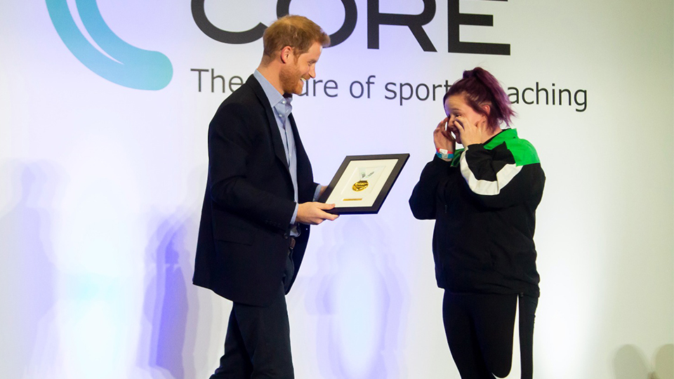 photo of Prince Harry awarding a graduating coach with an award at the ceremony at Loughborough University