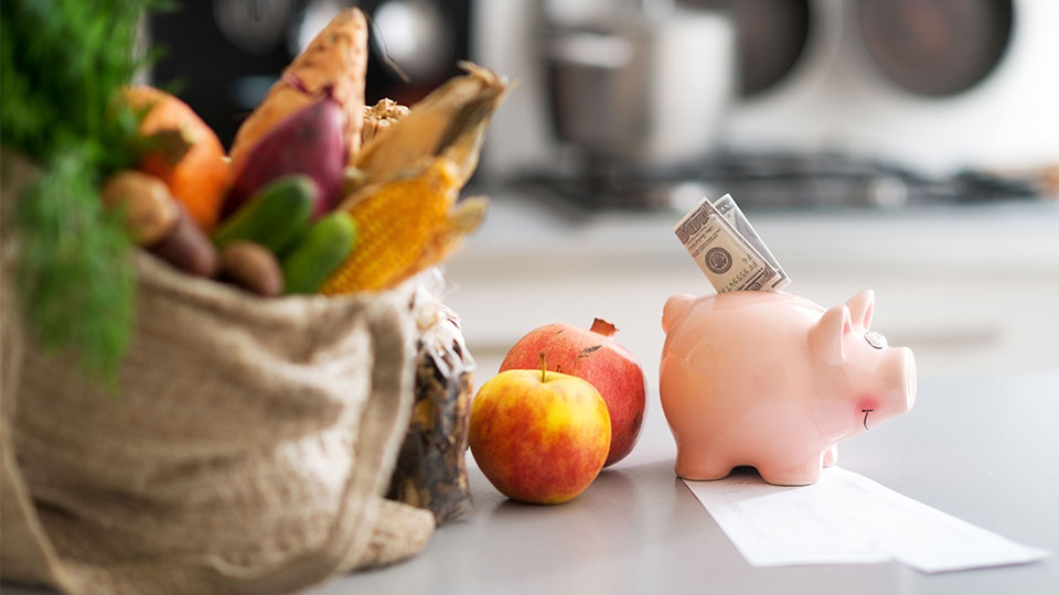 Photo of healthy food and a piggy bank with money