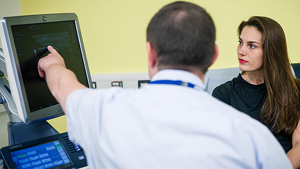 photo of NCSEM staff member and patient both look at a computer screen