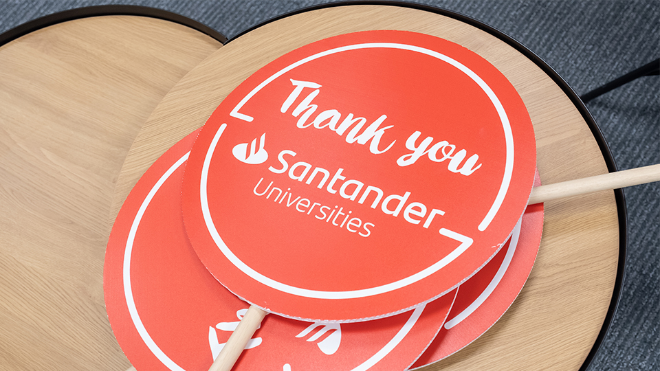 photo of red lollipop signs that say 'Thank you Santander Universities' in white writing