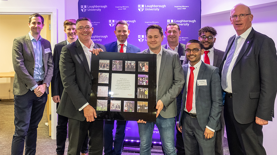 photo of Santander guests and University staff holding a plaque to acknowledge the 10-year partnership