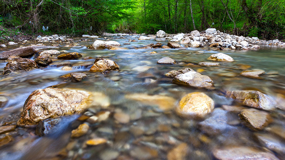 photo of riverbed with water flowing over rocks
