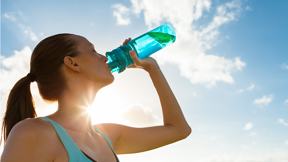 photo of a woman drinking water during exercise