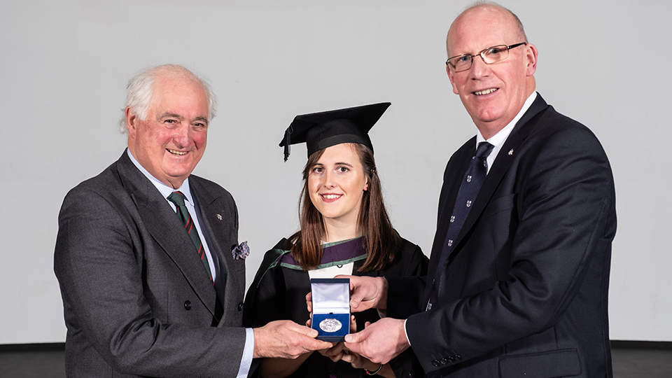 photo of female student being awarded with University prize by Professor Robert Allison
