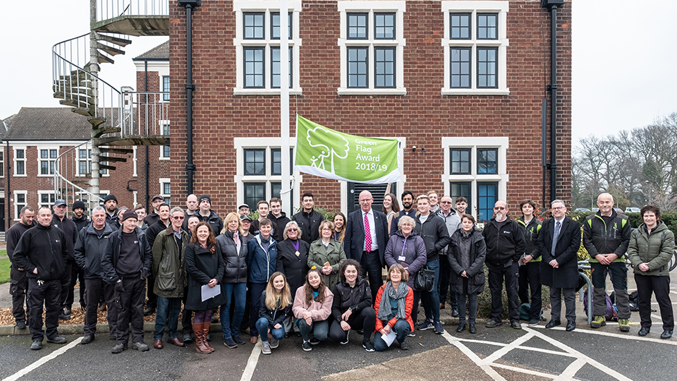photo of Green Flag and University staff and students outside Hazlerigg and Rutland buildings