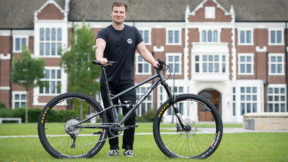 Photo of student Tom Bugler with his first bike design on the Hazlerigg lawn