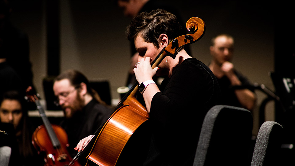 Photo of a man playing the cello at a concert