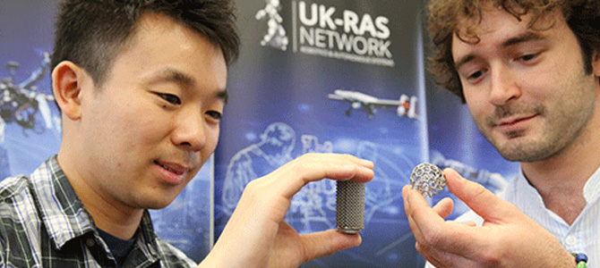 two researchers with the robotics items