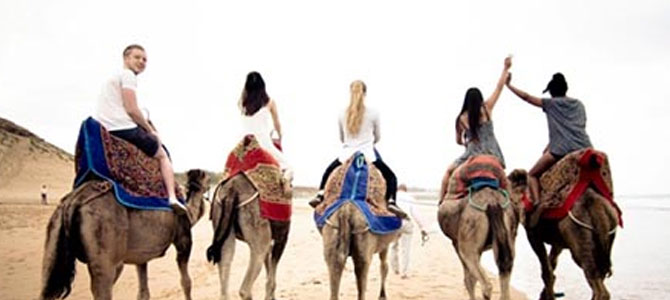 a group of five people riding camels