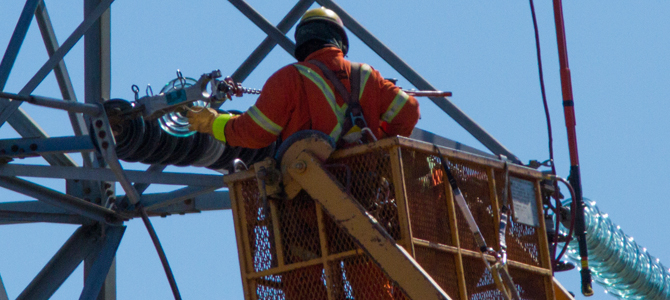 Technician in a cherry-picker, repairing a pylon