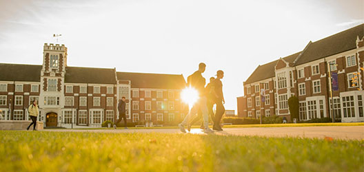 Students walking around the Hazlerigg Rutland area in sunlight