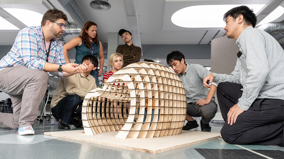 Photo of students from both universities and staff members looking at one of the models designed by a team at the Summer School