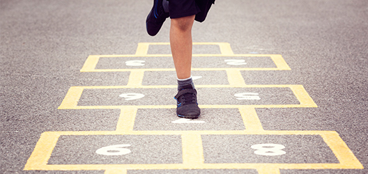 Pictured is a child doing hopscotch.