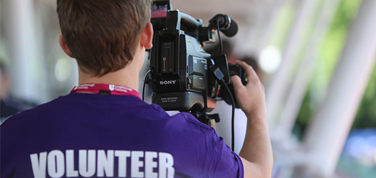 photo of a volunteer with a video camera wearing a purple top that says 'volunteer' on the back