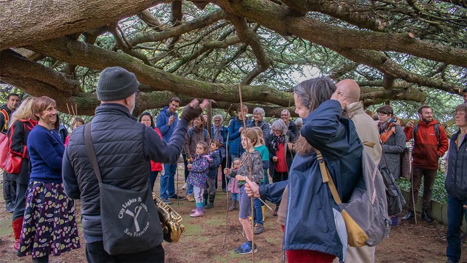 Photo of guests gathered by a tree outside during the Fruit Routes Harvest event