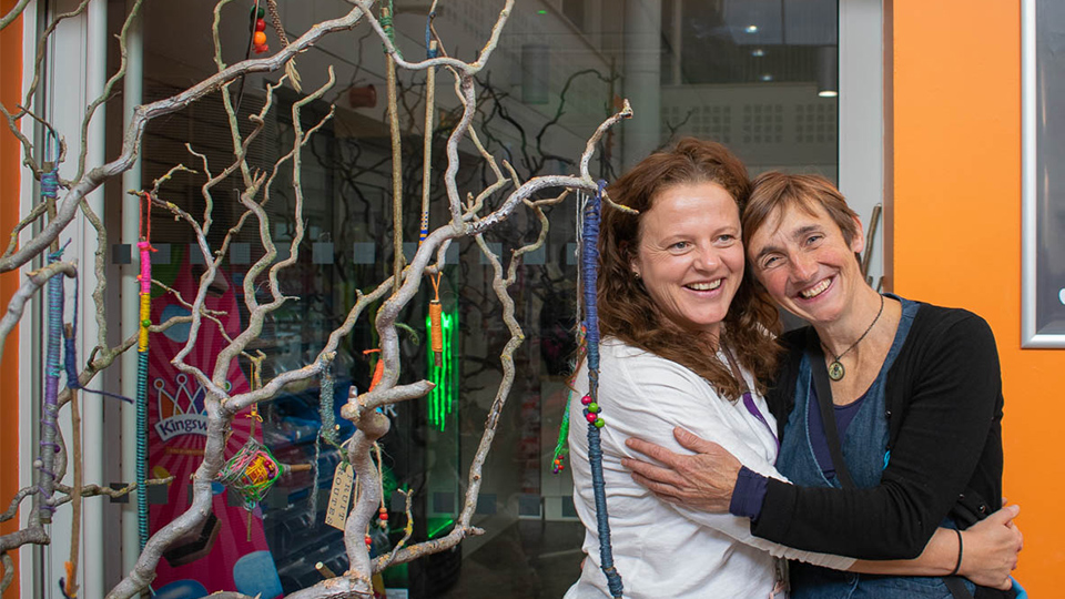 photo of artist Anne-Marie Culhane and Sustainability Manager Jo Shields hugging