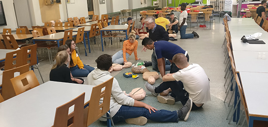 photo of students in halls being taught CPR skills by local organisation Heartwize