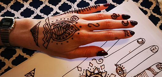 photo of a hand with henna on and a sketch of the design on paper